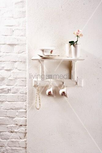 regal und hakenleiste mit tassen und perlenkette auf weisser wand bild kaufen living4media. Black Bedroom Furniture Sets. Home Design Ideas