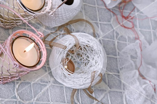 Top view of white lantern made of twine next to two lit candles in wire lanterns