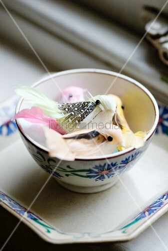 Pastel coloured decorative birds in a bowl