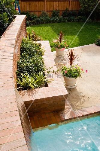 hochbeet mit ziegelmauer und terrasse vor pool im garten bild kaufen living4media. Black Bedroom Furniture Sets. Home Design Ideas