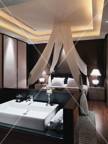Blick über Waschtisch auf Himmelbett mit Baldachin in klassisch ...