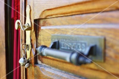 Old wooden door with brass door handle and key in lock