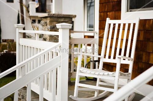 ein weisser schaukelstuhl auf der veranda bild kaufen living4media. Black Bedroom Furniture Sets. Home Design Ideas