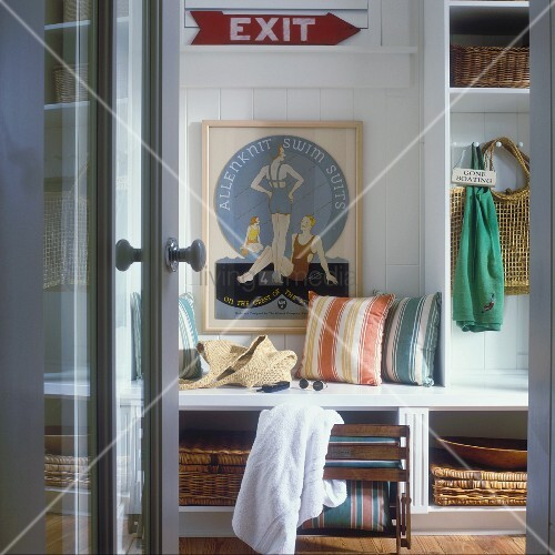 Cloakroom of beach house with storage room and framed poster with swimming motif