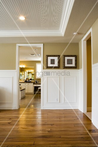 Image of empty room with wood floor looking into another room.