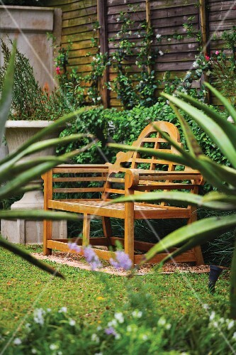 A wooden garden bench in a garden