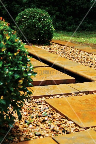 Watercourse constructed from stone flags and gravel next to box ball in garden