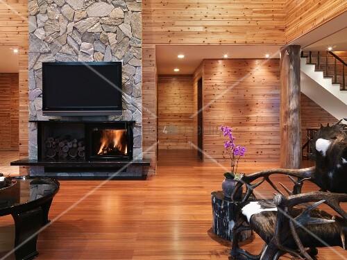 minimalistischer wohnraum mit holzverkleideten w nden und rustikaler stuhl mit fellsitzfl che. Black Bedroom Furniture Sets. Home Design Ideas