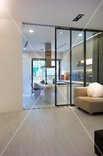 Armchair in front of a glass wall in a minimalist lobby with a view through open sliding doors into a white designer kitchen