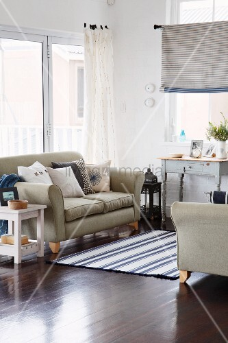 Light-flooded seating area with two sofas accessorised with blue and white cushions and woven rug