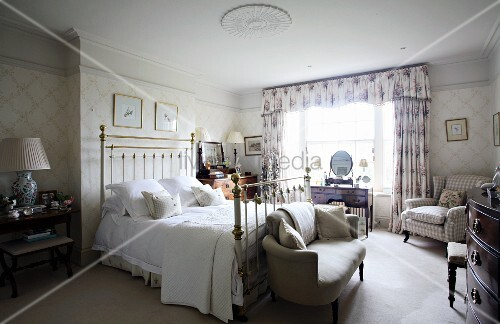 Antique country-house bedroom with metal four-poster bed, upholstered furniture and floral curtains with pelmet