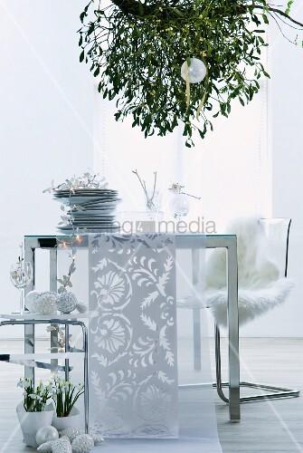 tellerstapel und tischl ufer auf modernem tisch unter misteln von decke abgeh ngt bild kaufen. Black Bedroom Furniture Sets. Home Design Ideas