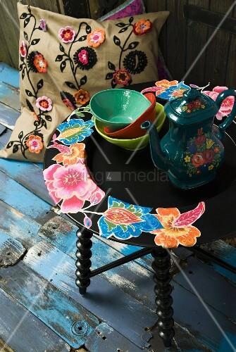 Blümchenkanne auf Beistelltisch mit Blütenmotiv und Kissen mit gehäkelten Blumen Applikationen