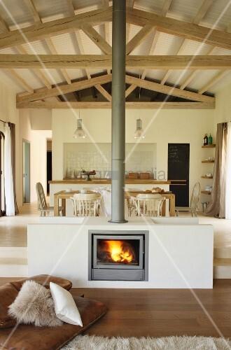 Eingebauter Kamin In Wohnzimmermitte Vor Essbereich Und Küche Auf Podest In  Offenem, Mediterranem Haus
