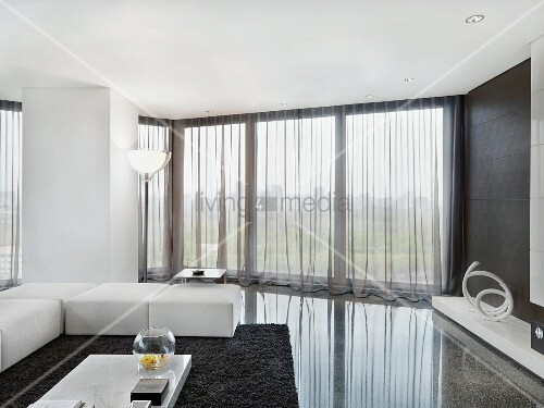 Elegant White Upholstered Living Room Furniture On A Polished Stone Floor  In A Minimalist Living Room With See Through Curtains In Front Of A Bank Of  ...