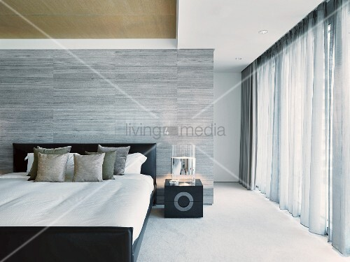 Elegantes Designer Schlafzimmer Mit Doppelbett Vor Gefliestem Raumteiler In  Grau Neben Bodenlangen Vorhängen Am Fenster