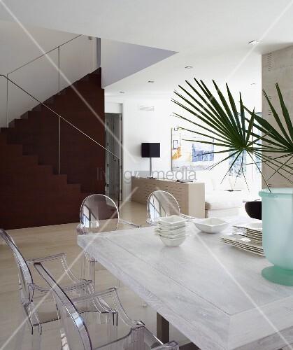essplatz mit acrylglas st hlen ghost an weiss lasiertem tisch skulpturale treppe als dunkler. Black Bedroom Furniture Sets. Home Design Ideas