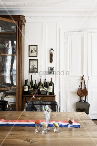 Wooden table with a Tricolor banner, in the background and side table with wine bottles and an antique armoire