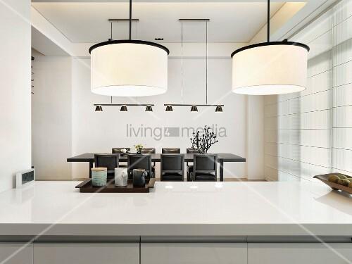 designer h ngelampe mit weissem schirm ber k chenblock und blick auf essplatz bild kaufen. Black Bedroom Furniture Sets. Home Design Ideas