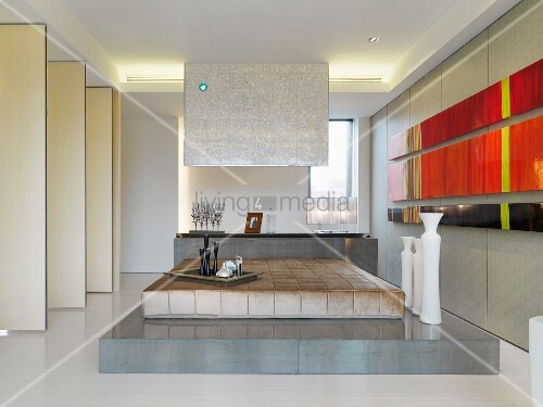 Modernes Schlafzimmer mit Bett auf Podest neben abstrakten Bildern ...