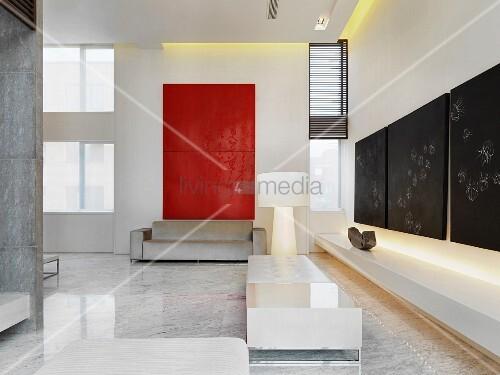 Designer Couchtisch Und Helle Sitzmöbel Auf Marmorboden Vor Modernen Bildern  An Wand