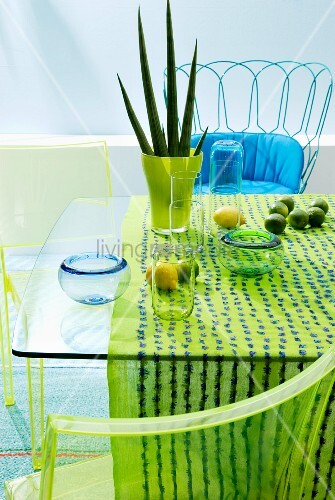 Ornaments in shades of aqua on glass table, wire chair with blue seat cushion & green plexiglass chairs