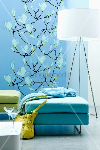 Ottomans in shades of aqua in front of designer standard lamp; blue wall-hanging with magnolia blossom pattern in background