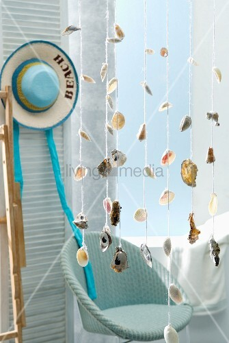 Seashells strung on cords hanging from ceiling in front of wicker chair