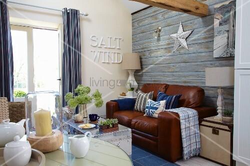 Wohnzimmer Im Maritim Stil Mit Ledercouch Vor Der Tapezierter Wand In  Holzoptik