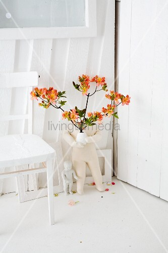 Rhododendron (variety: 'Coccinea speciosa') in vase on floor next to white kitchen table