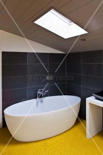 minimalistische badewanne unter einer dachschr ge mit fenster ffnung bild kaufen living4media. Black Bedroom Furniture Sets. Home Design Ideas