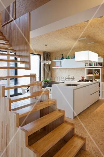 Moderne Treppe aus Holz in offenem Wohnzimmer und Blick auf ...
