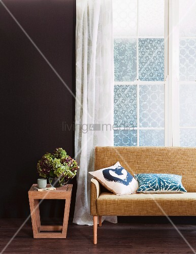 moderner beistelltisch aus holz mit blumenstrauss neben sofa im fiftiesstil vor fenster mit. Black Bedroom Furniture Sets. Home Design Ideas