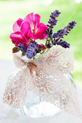 Glass with lavender and geraniums, tied with decorative ribbon