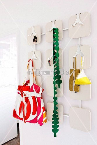 Ladies' accessories and keys hanging on white retro coat rack with shiny metal hooks