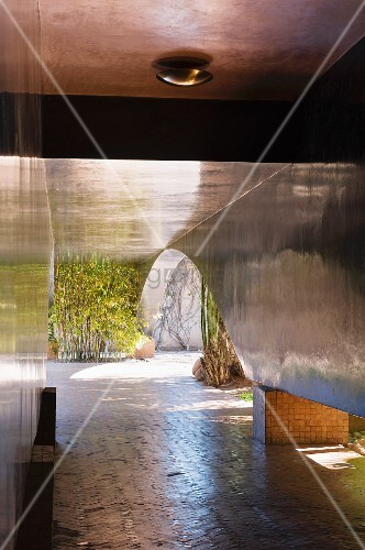Tunnel-like entrance walkway composed of dark polished curved walls raised on square tiled plinths