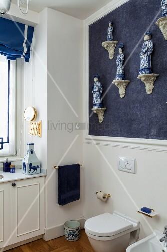 Helle Badezimmerecke Mit Einer Sammlung Chinesischer Porzellanfiguren An  Blauer Wand