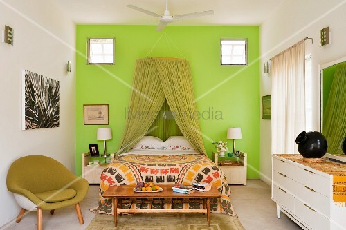 Schlafzimmer Mit Grünem Moskitonetz über Dem Doppelbett Vor Grüner Wand  Davor Ein Grüner Schalensessel Und Ein Weißes Sideboard
