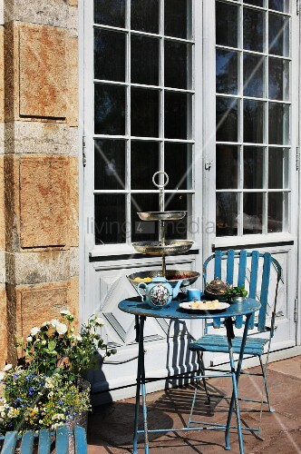 vintage gartenm bel aus blau lackiertem metall vor der terrassent r eines alten hauses teatime. Black Bedroom Furniture Sets. Home Design Ideas