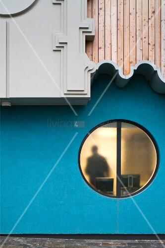 Post modern house facade with a round window and overhanging, ornamental wall elements (BBC Cardiff)