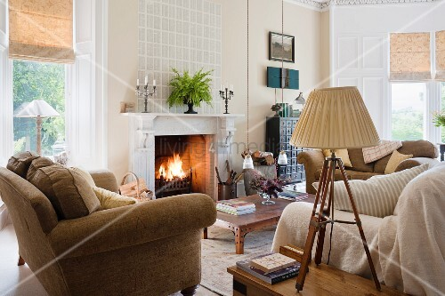 Fired Earth sofas in living room with fireplace and lamp on a wooden antique tripod stand. The walls are painted in String by Farrow and Ball.
