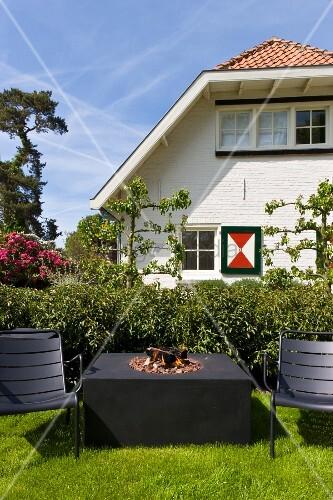 minimalistischer tisch mit feuerstelle und gartenst hle in schwarz auf dem rasen vor. Black Bedroom Furniture Sets. Home Design Ideas