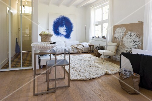 Large living room with a modern table and chair in front of lounge area with light rug and portrait drawing on the wall