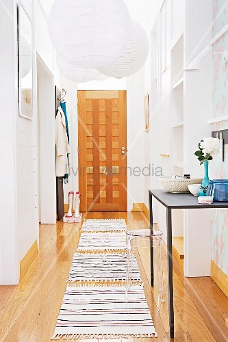 Narrow hallway with white, paper pendant lamps above rugs on wooden floor and wooden front door at far end