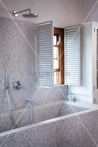 badewanne und wand mit hellen mosaikfliesen und offene innenl den am fenster in modernem bad. Black Bedroom Furniture Sets. Home Design Ideas