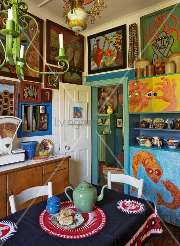 Artistically inspired kitchen decor with naïve, South African paintings on walls and tablecloth with ethnic pattern