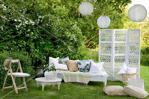 Romantic, white seating area in garden - bench with cushions and folding chair around side table next to screen below lanterns hanging in tree
