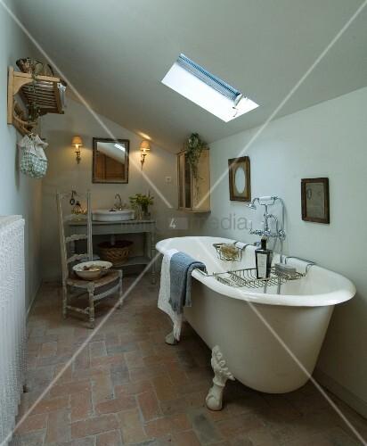 freistehende antike badewanne unter der dachschr ge in einfachem badezimmer eines. Black Bedroom Furniture Sets. Home Design Ideas