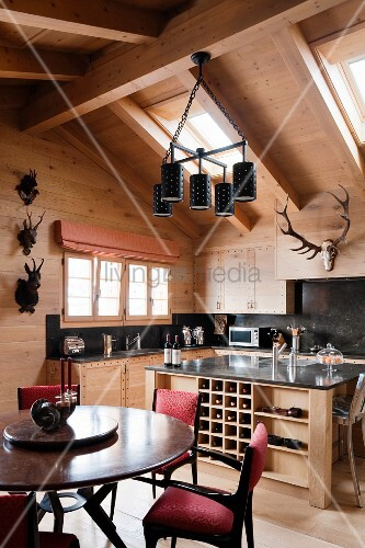 Round dining table and upholstered chairs in front of island counter and open-plan kitchen in attic storey of wooden house