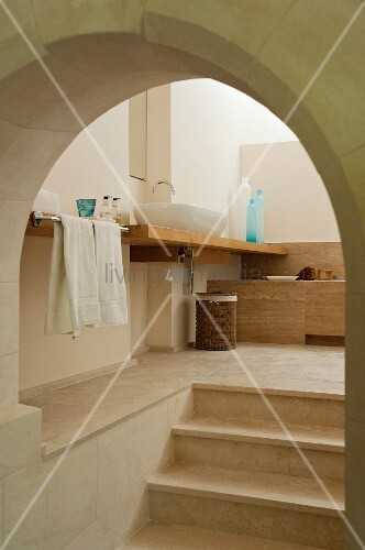 View of stone steps leading through arched doorway to modern ensuite bathroom